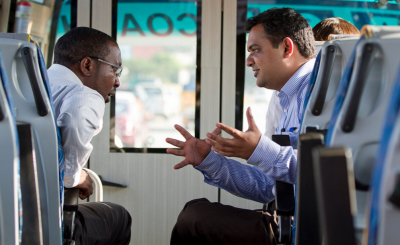 Vincent Mutugi of Access Afya (left) and Nikhilesh Ghushe of Swasth India (right) take advantage of time on the bus to discuss their models.