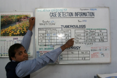 A health worker in Bangladesh showing tuberculosis case detection information on a whiteboard. WHO/G Hampton